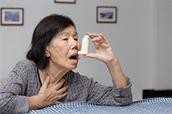 old woman about to take her inhaler