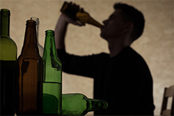 bottles with silhouette of a guy drinking in the back