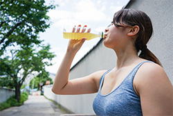 woman wearing a tangtop having a cold drink