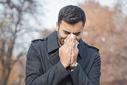 a guy sneezing in a napkin