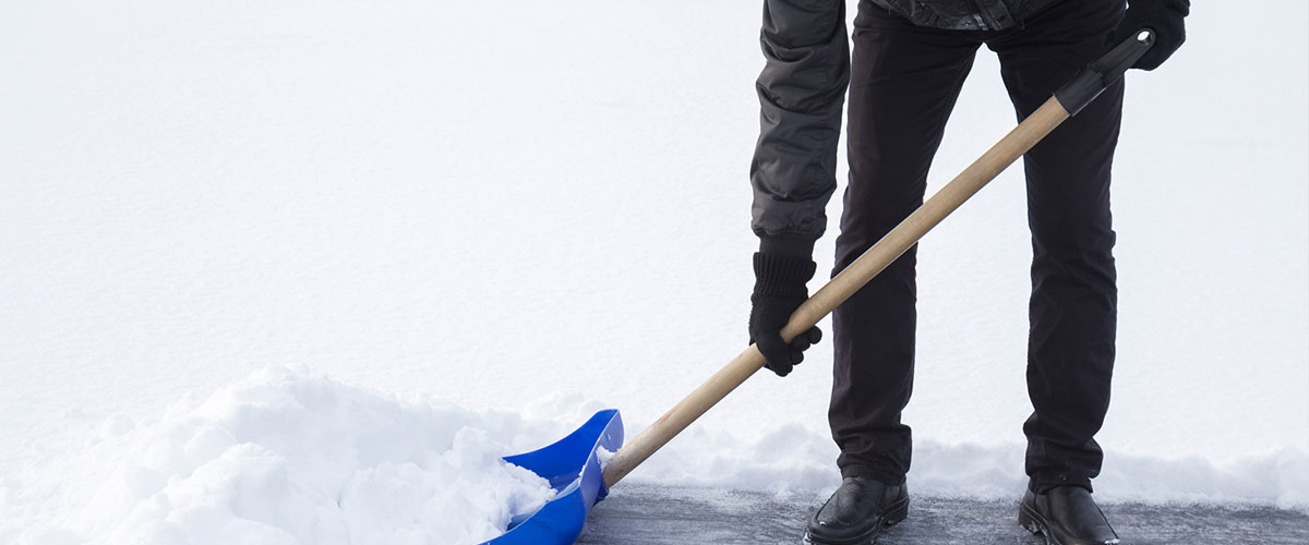 An adult shoveling snow