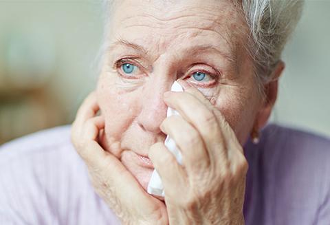 older woman wiping away tears