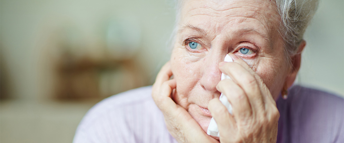older woman wiping face with tissue