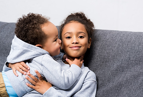 african american sister sitting on sofa with her little brother at home