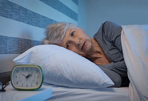 Worried senior woman in bed at night suffering from insomnia.