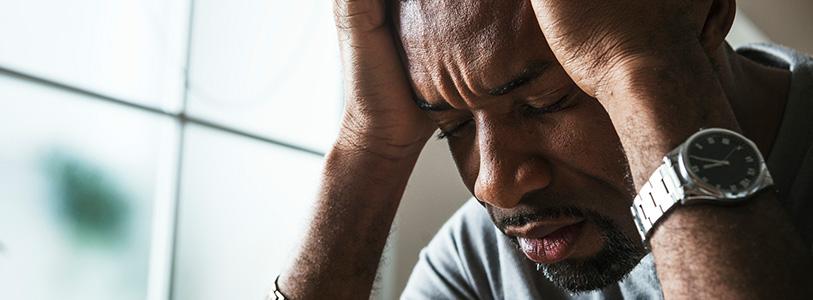 black man holding his head