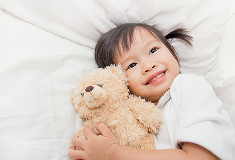 asian child hugging teddy bear in bed