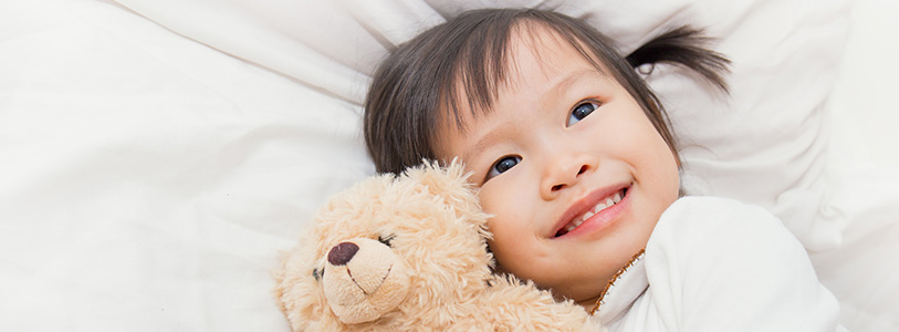 asian child holding stuffed animal in bed