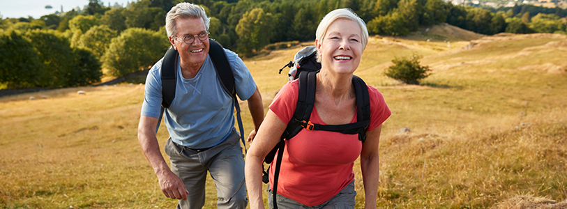 Senior couple climbing a hill on a hike through the countryside