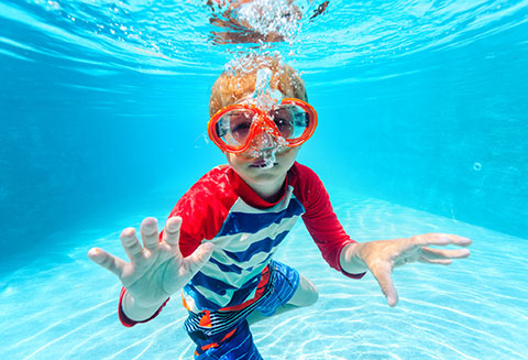 boy wearing goggles underwater