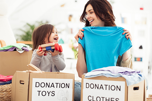mother and child holding donation clothes and toys