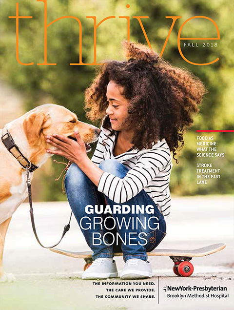 Thrive Magazine Fall 2018 Cover: Young African-American girl sits on a skateboard and pets a golden retriever dog