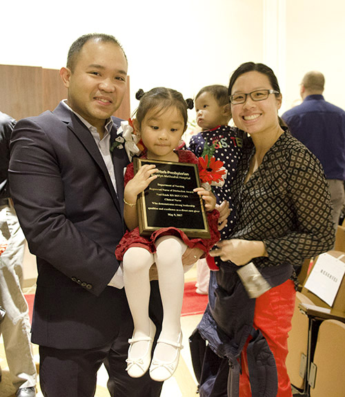 Noel Emde, R.N., critical care nurse, won the Nurse of Distinction Award and celebrated with his wife and children.