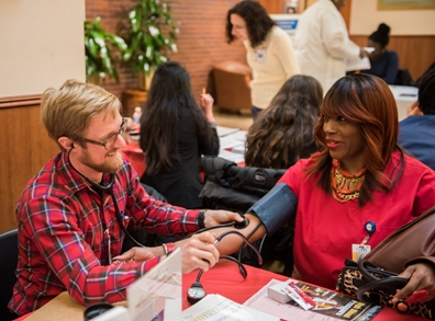 Nursing student and NYM volunteer Nicholas Warndorff (left) takes a blood pressure reading at the Hospital
