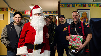 Santa and firefighters from Ladder Company 122, Engine Company 220 and Tower Ladder 131 visit children at NewYork-Presbyterian Brooklyn Methodist Hospital.