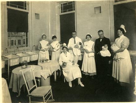 Doctors and nurses, c. 1919, hold newborns in the maternity ward nursery.