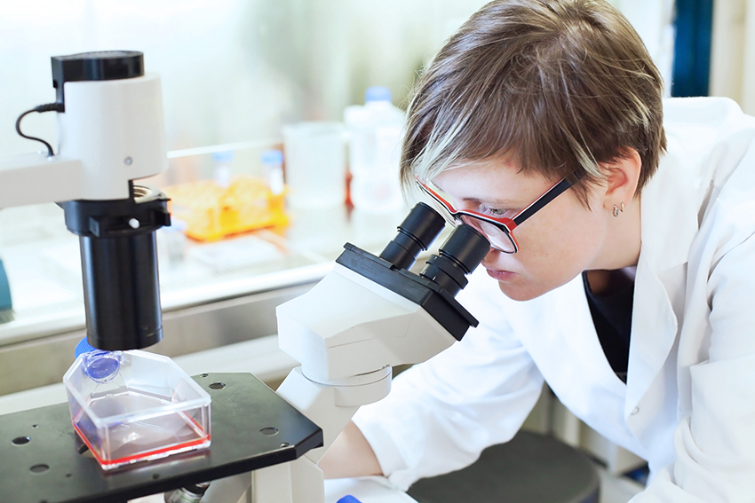 image of scientist looking into microscope