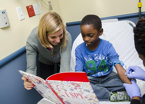 Child Life specialist reading a book to pediatric patient whom is getting their blood drawn