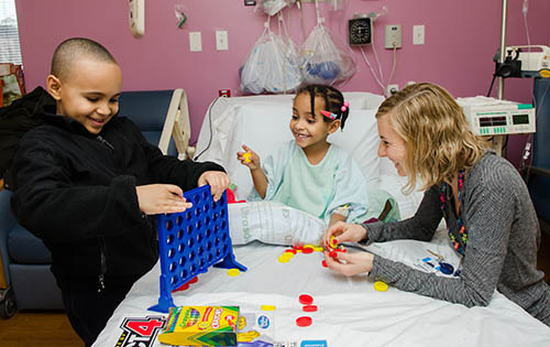 Child Life Specialist playing board games with a pediatric patient and her brother