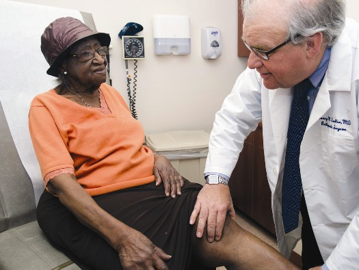 Doctor examining patient's joints around the knee