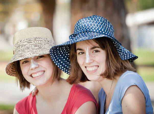 Young women wearing sunscreen on their noses.