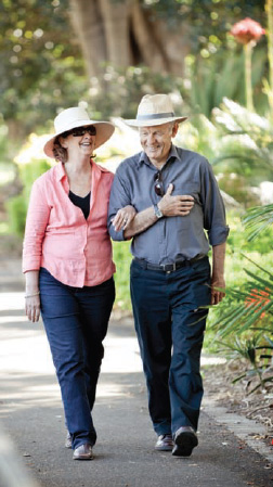 Couple wearing hats with protective sun visors outdoors.