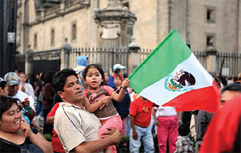 Picture of a Mexican father holding his daughter with a mexican flag