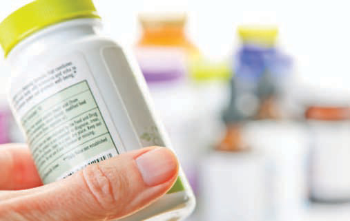 close up, hand holds bottle of pills
