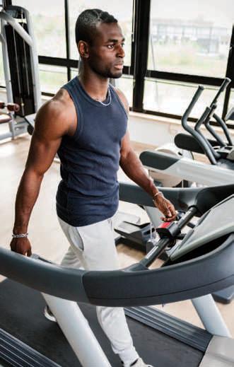 man walks on treadmill at gym