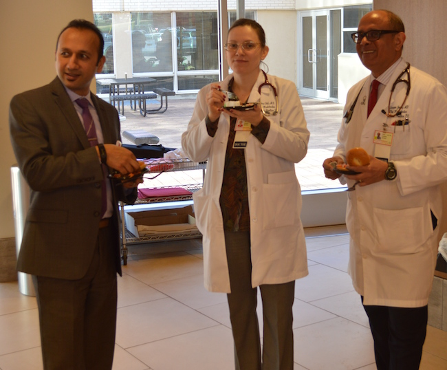 Hospitalists eating cake at Doctors Day celebration.