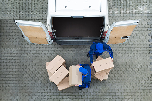 Birds-Eye view of guys taking out cardboard boxes from a van