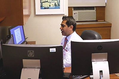 image of Dr. Sharma in front of computer monitors