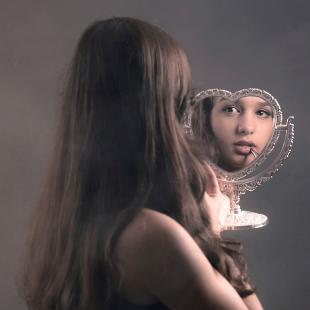 Young woman staring in mirror as she applies makeup