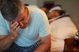 man at edge of bed, unable to sleep