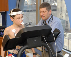 Boy on treadmill with physician beside him