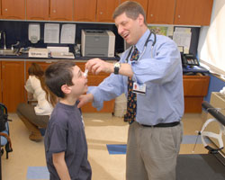Doctor tests a boy's breathing