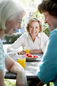 three senior women laugh at an outdoor table
