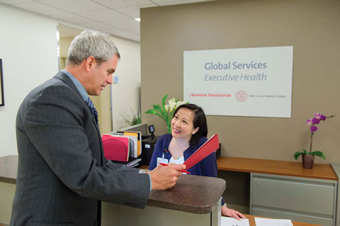 patient talks with receptionist at Executive Health at New York Presbyterian