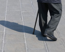 Older man walks with cane
