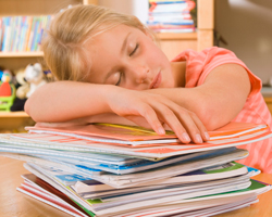 Girl sleeps on stack of books