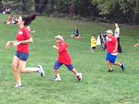 children and teacher run on grass