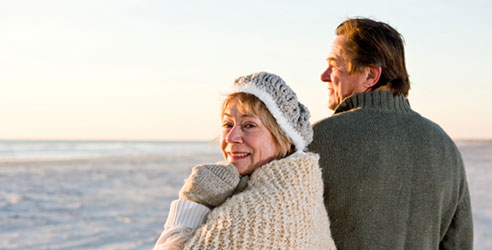 an older couple stands on the beach in winter