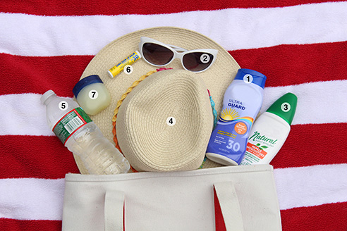 beach supplies such as a towel, sunglasses, and sunscreen