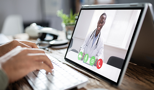 image of person typing on keyboard in front of doctor on a screen