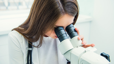 image of woman looking into microscope