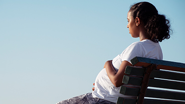 image of blue skies and pregnant woman sitting on bench